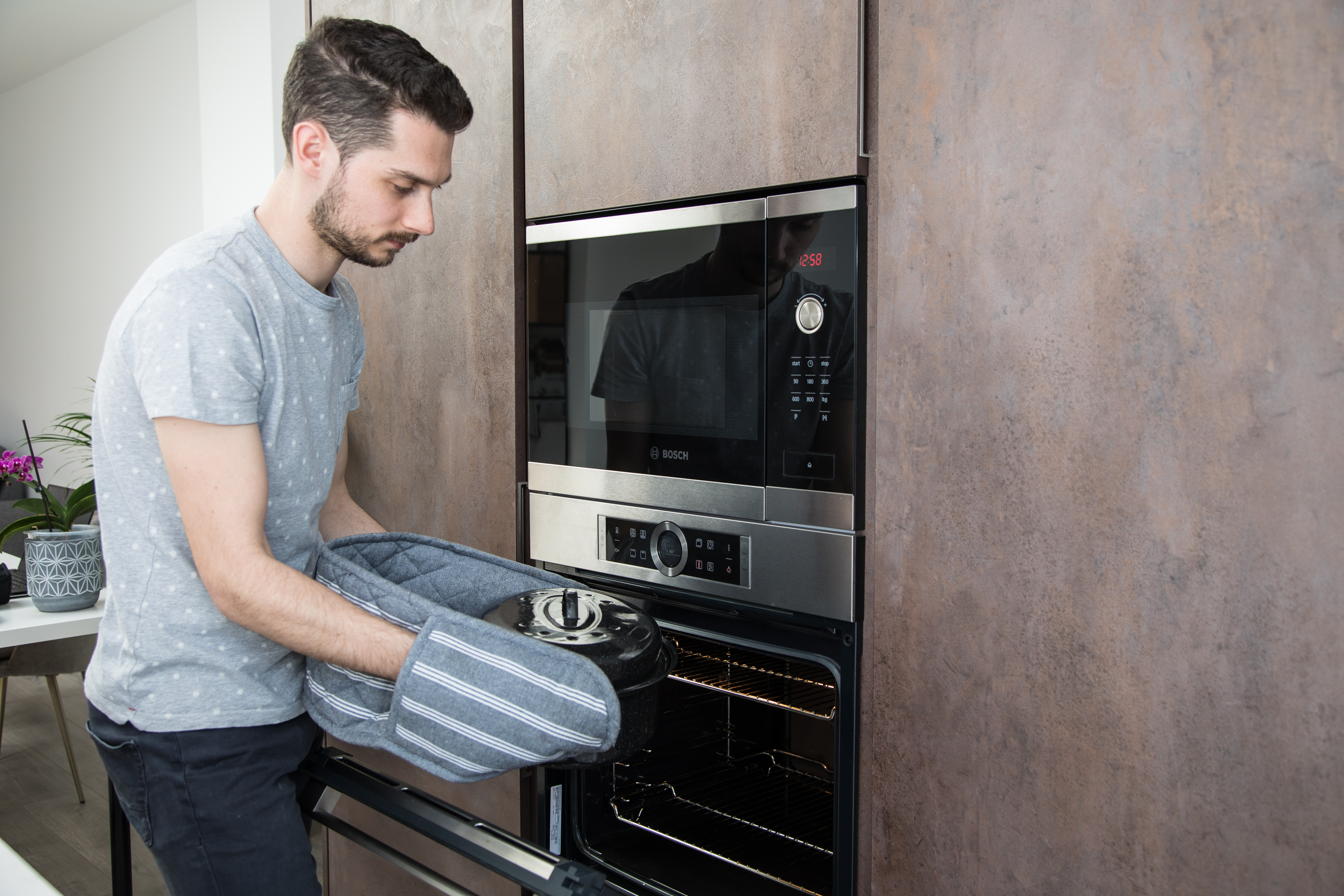 Man taking pot out of the oven